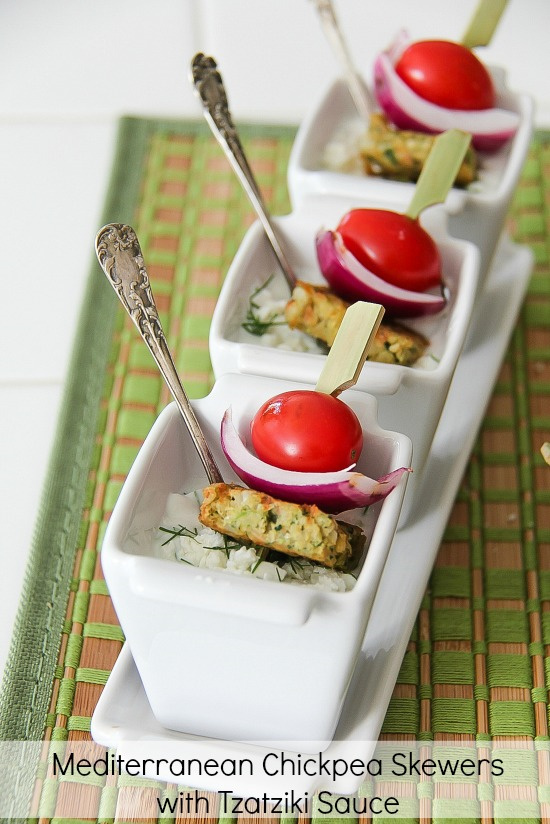 chickpea patties on skewers with red onion and tomato in a tzatziki dipping sauce