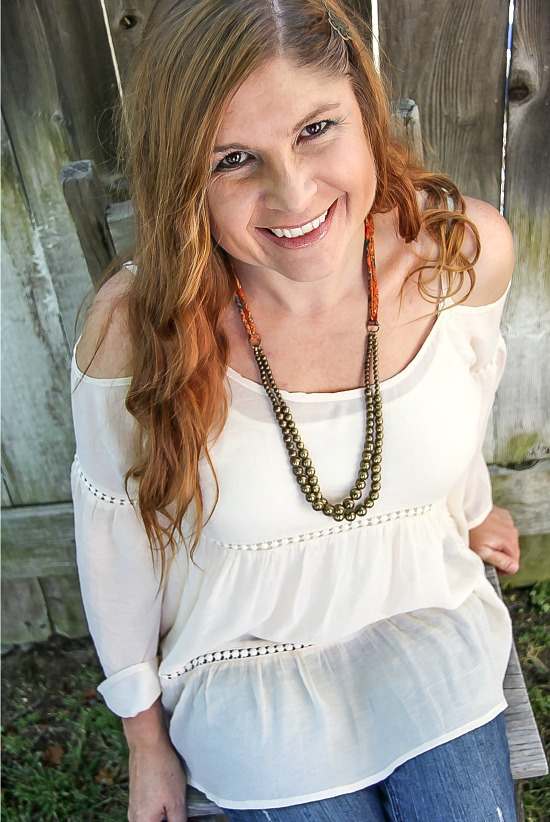 lady wearing a cream cold shoulder boho top with flared sleeves