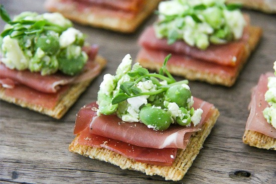 Triscuit crackers with prosciutto, pea shoots, feta cheese, and peas