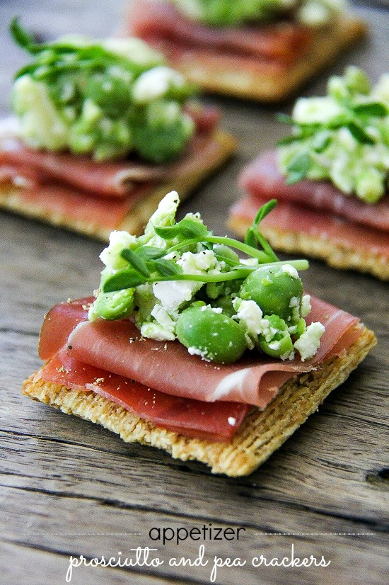 prosciutto on crackers topped with peas, feta cheese, and microgreens