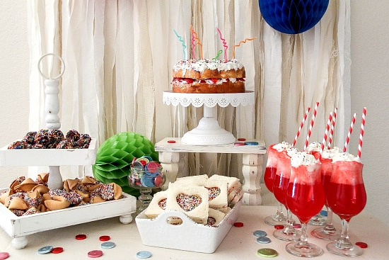 a food party table with angel food cake, doughnut holes, ice-cream floats, fairy bread, and fortune cookies