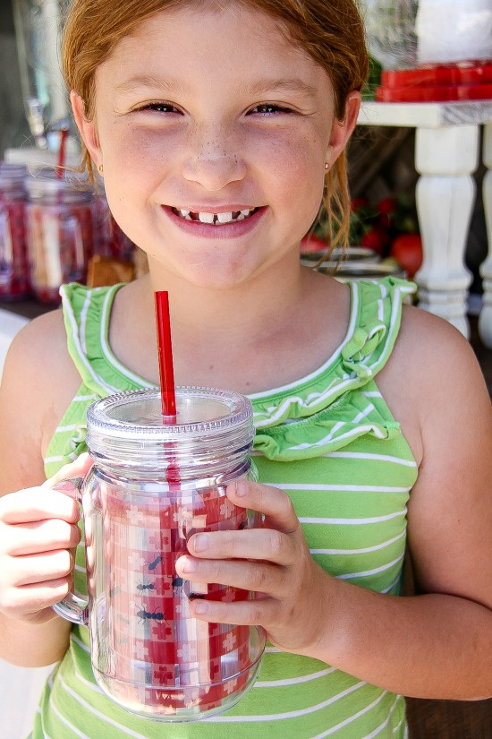 a girl holding a picnic themed cup with a straw that looks like a picnic blanket with ants crawling on it