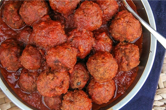 meatballs with a red sauce in a bowl for serving