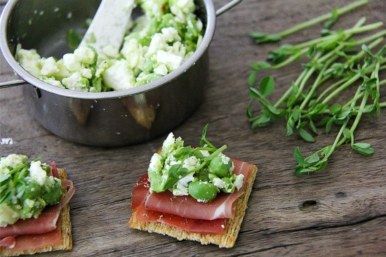 crackers topped with prosciutto, peas, feta cheese, and greens