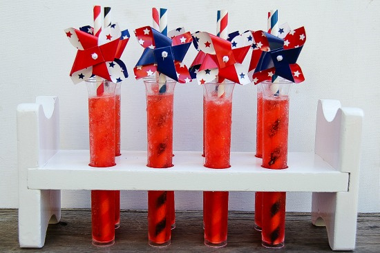 a white test tube stand with red white and blue test tube drinks in it for a patriotic party