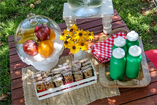a wood table with flowers, fruit, granola bars and a water dispenser for kids