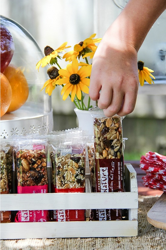 a child's hand reaching for a Taste of Nature granola bar