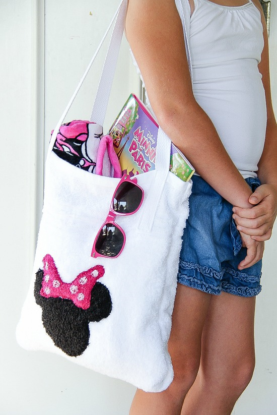 a girl holding a white toweling bag with minnie mouse on it