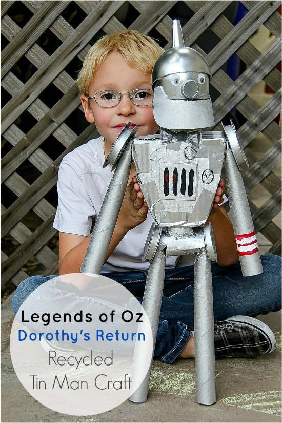 a boy holding a Tin Man from the Wizard of Oz that was made out of recycled materials