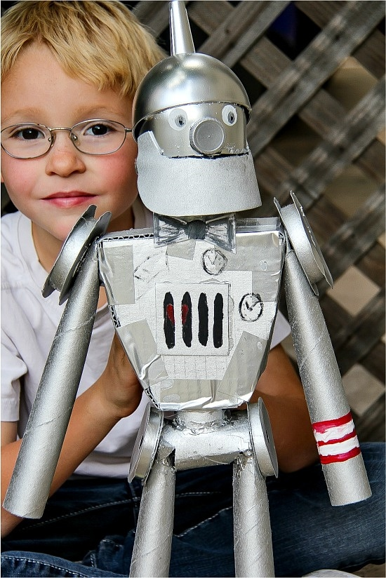 a boy holding a tin man that he made out of recycled materials