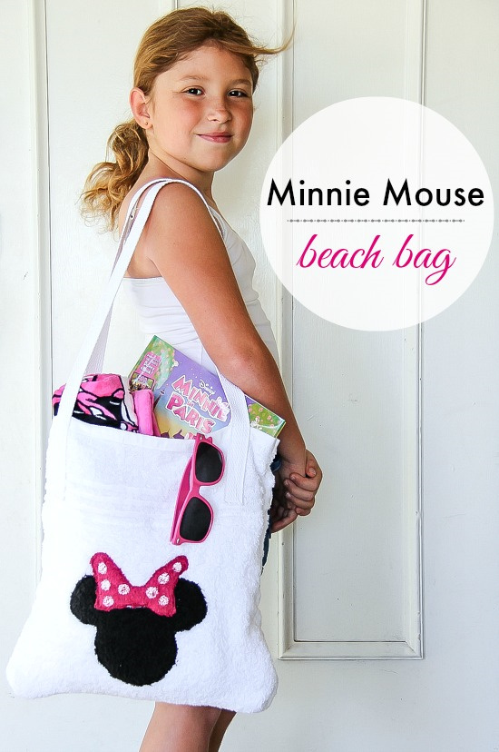 a girl holding a Minnie Mouse beach bag filled with beach stuff.