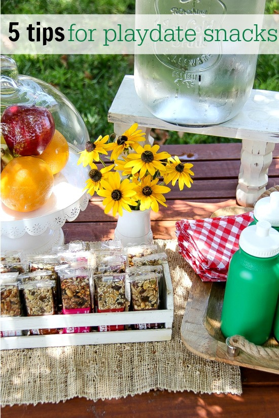 a snack table for kids with fresh fruit, water, and taste of nature bars