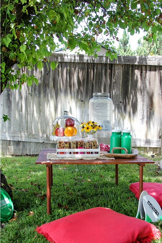 a small table set up in a backyard for kids that has healthy snacks and water