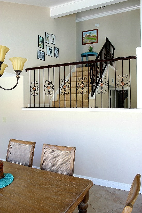 dining table with a staircase and photos on the wall