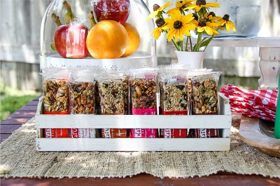 granola bars in a white wood snack holder with fresh fruit and flowers