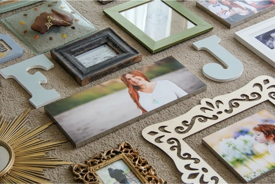photos being laid out on the ground for a gallery wall