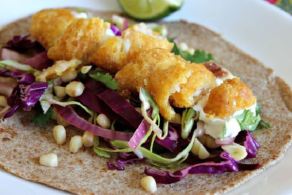 beer batter fish tacos on cabbage and corn with lime and cilantro