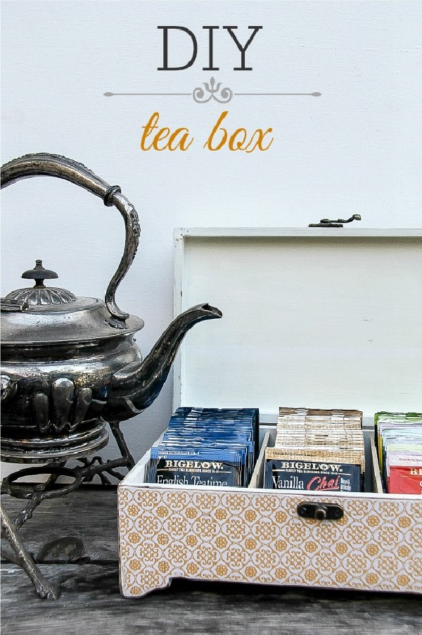 an orange and white wood tea box with an antique silver tea pot