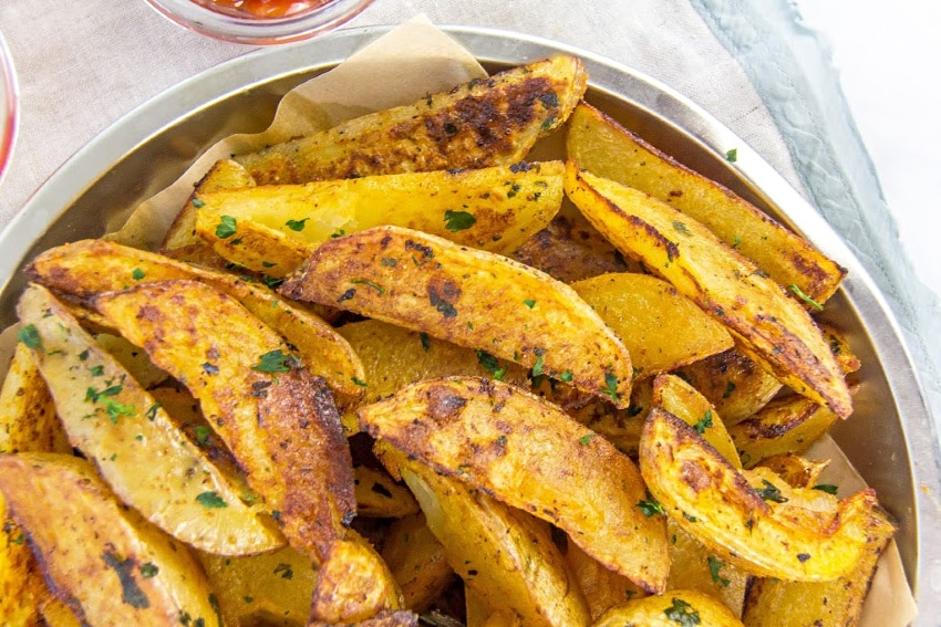 seasoned potato wedges in a silver tray with parchment paper