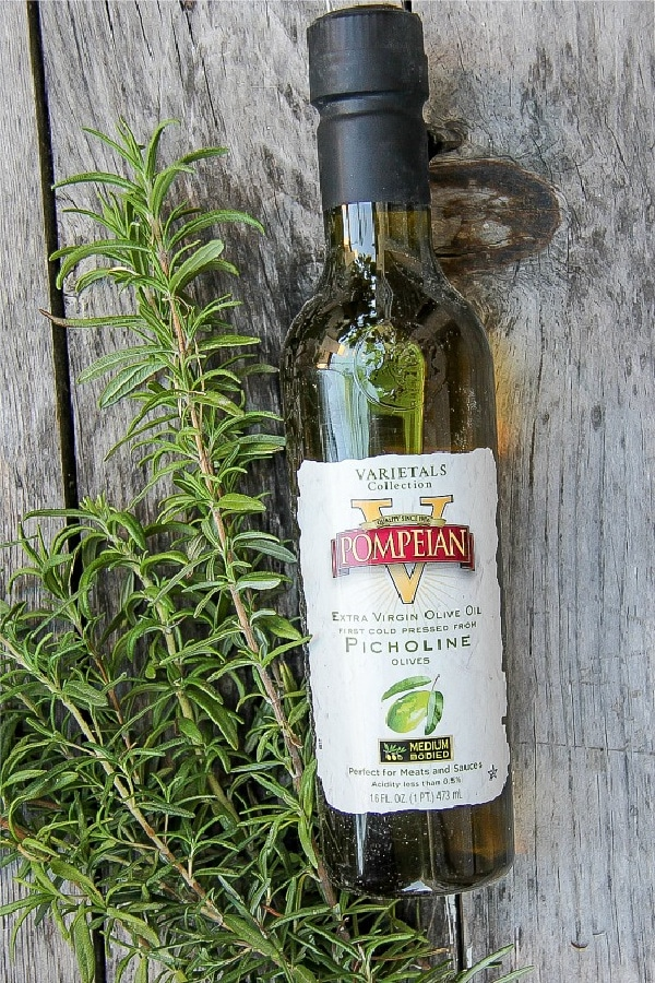 a bottle of Pompeian olive oil and a bunch of fresh rosemary