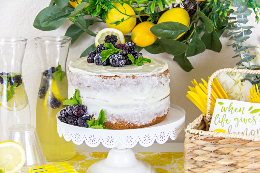 naked cake topped with blackberries and lemon with a lemon cocktail and lemon party table supplies
