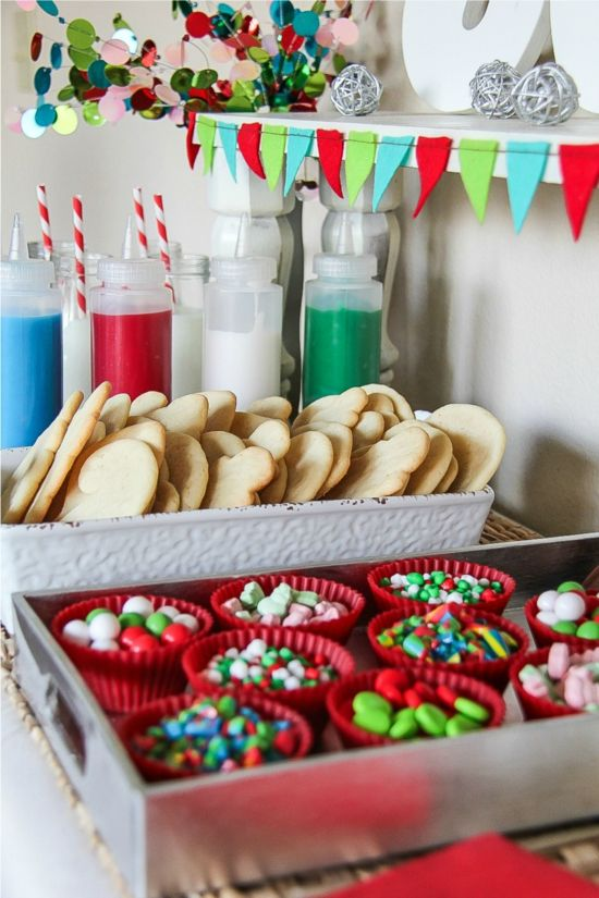 christmas sugar cookies, toppings in red cupcake liners, and icing in bottles for a christmas cookie decorating party