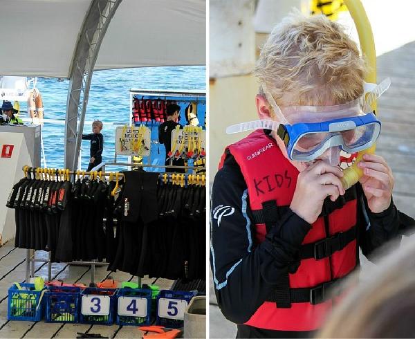 boy trying on snorkeling gear on a great barrier reef pontoon