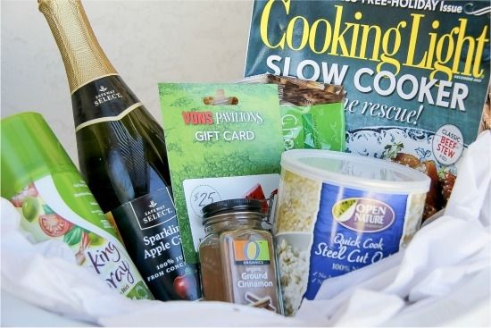 apple cider, a gift card, magazine with recipes, and food items inside a slow cooker for a gift