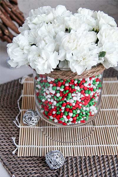 a vase filled with candy and flowers for a christmas centerpiece