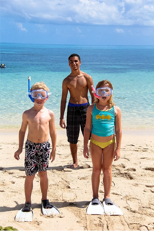 kids on the beach getting ready to snorkel off green island