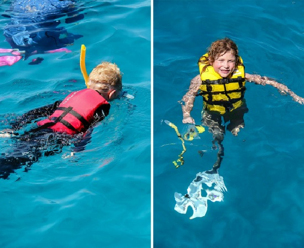 kids snorkeling in the blue water at the great barrier reef