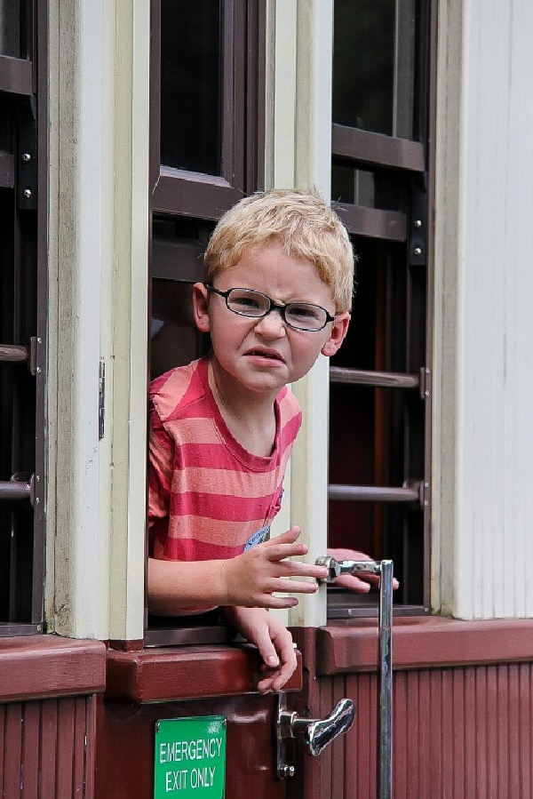 a boy pulling a face while hanging out the window of a train