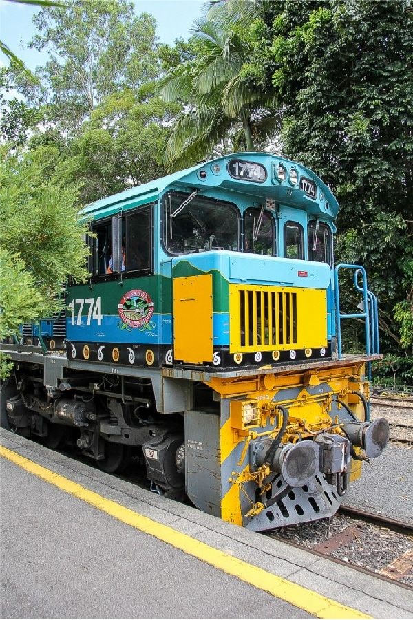 a blue, yellow, and green train that goes to Kuranda Village