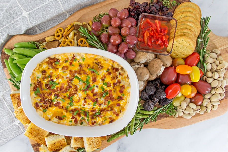Kentucky Hot Brown dip on a holiday charcuterie board with tomatoes, crackers, Texas Toast squares, fruit, and pistacchios.