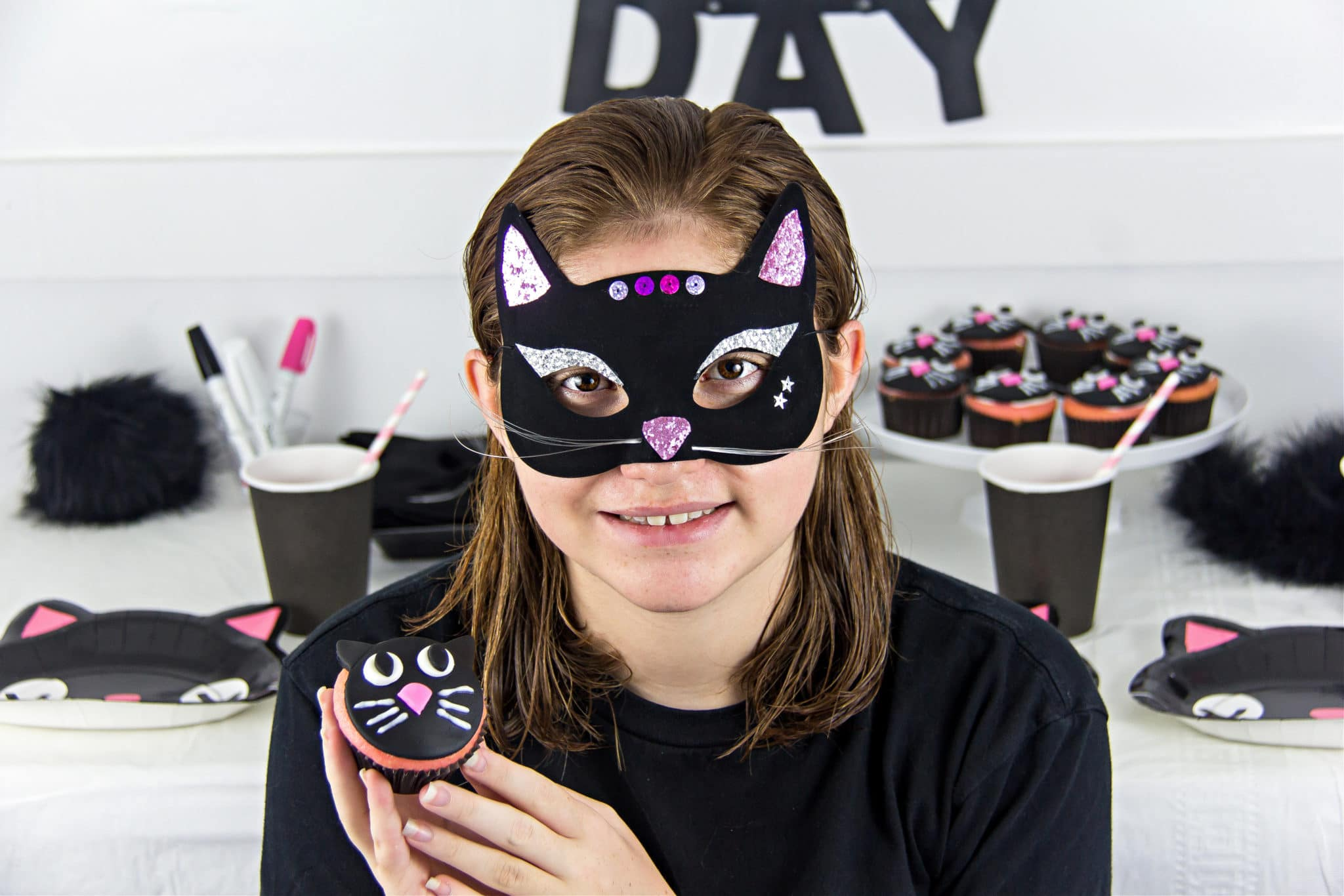 a girl wearing a black cat mask and holding a black cat cupcake