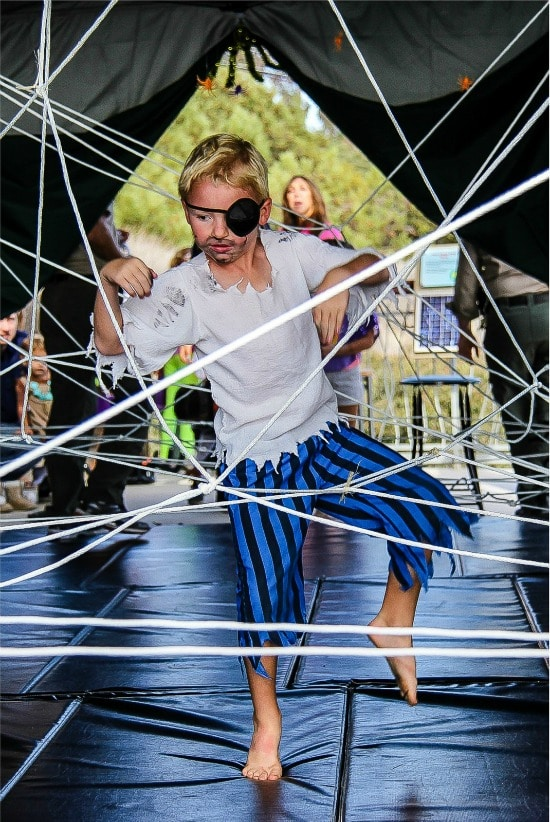 boy dressed in a pirate costume going through a spider web maze of ropes
