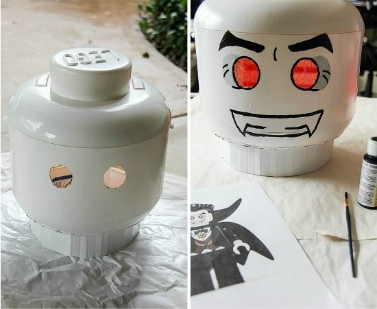 a yellow lego man storage bin painted white and turned into a vampire costume head