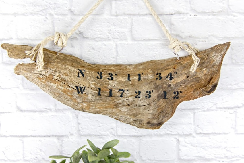 driftwood with beach coordinates on it