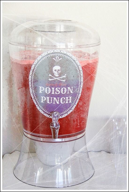 red punch in a drink dispenser with a poison punch label on it for Halloween