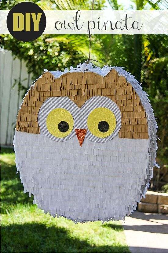 a white and yellow handmade owl pinata hanging in a backyard