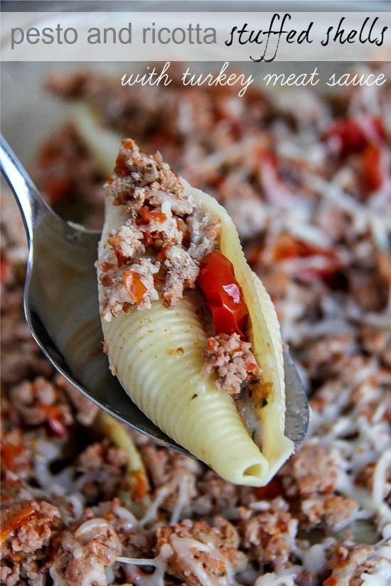 a spoon holding jumbo shell pasta stuffed with ground turkey, pesto, and ricotta