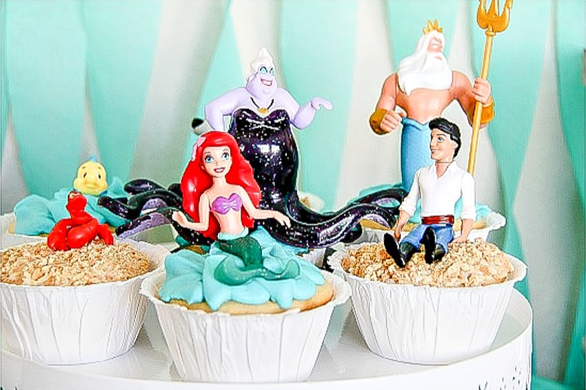 Little Mermaid cupcakes with toys on top of them.