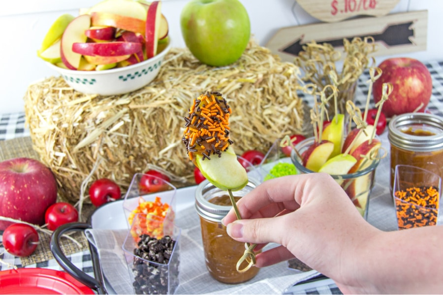 hand holding a caramel apple slice in front of a caramel apple dipping party table