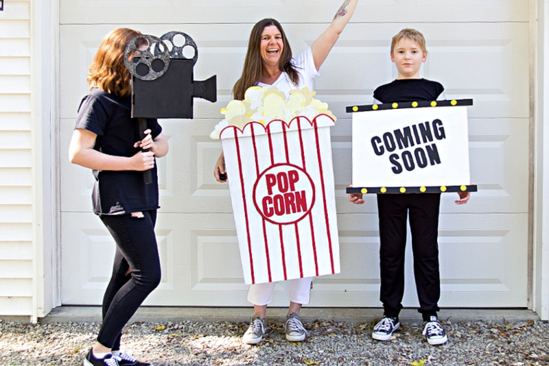Family costume idea including popcorn, movie screen and movie projector made out of Amazon Prime cardboard boxes.