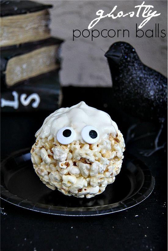 Popcorn balls dipped in white chocolate and shaped like ghosts for Halloween