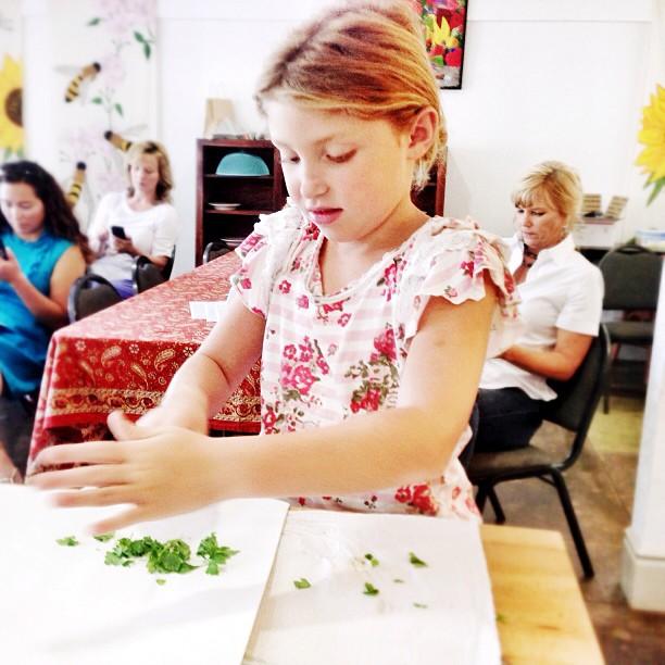 girl chopping herbs for homemade hummus