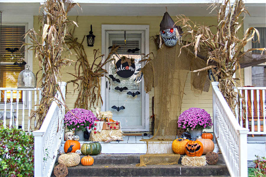 A haunted orchard themed front porch decorated for Halloween.