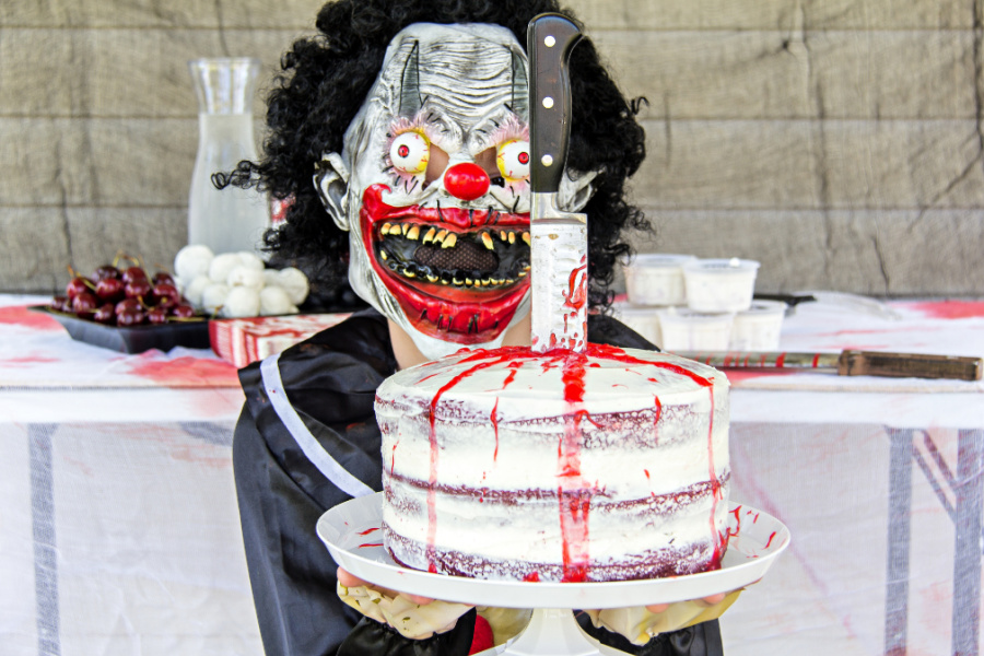 A boy wearing a slasher costume and holding a red velvet naked cake with a knife and blood on it.
