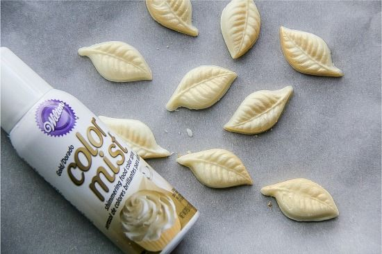 white chocolate leaves being sprayed with edible gold spray to make gold wings