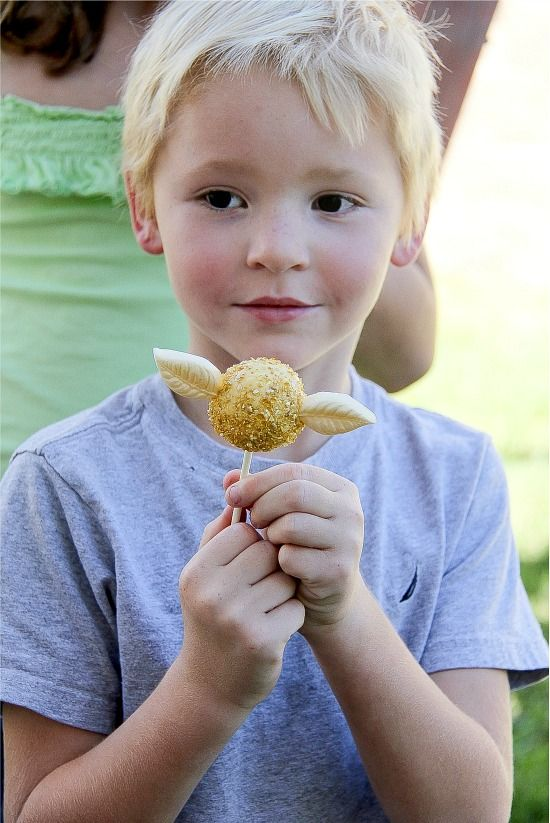 boy holding a golden snitch cake pop at a harry potter party
